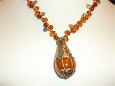 What a stunner. I strung golden Teardrop Beads alternating with Silver Leaves and tiny Silver Spacers on a wire to enhance the gorgeous Tibetan Amber Pendant. The Pendant is 2 long, and about 1 wide,handhammered silver caps with silver wires hold the Tibetan Amber drop in place.   Measured outstretched, the necklace is 191/2, the Pendant2, by 1 and it hangs down 11. (In the last photo you get a better idea about the sizewith a nickel placed in the middle)   Great for the Opera, the Bride...