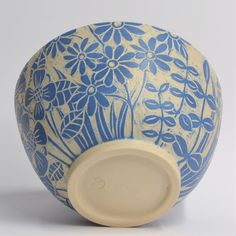 Handthrown bowl with sgraffito decoration of flowers and leaves in blue.