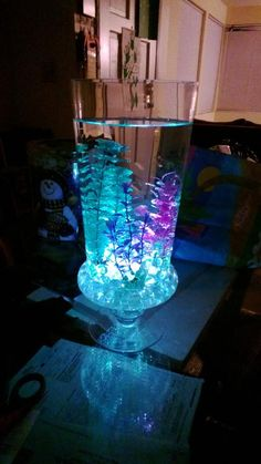 5 to 10 dollar glass vase from Walmart stones and glow sticks from dollar store and fish tank plants or water proof LED light that change color (for light if don't want to use glow sticks) all this makes you a wonderful center piece