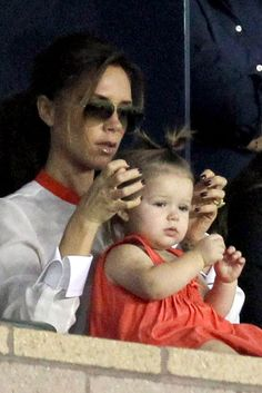 El estilo de Harper Beckham. Victoria y Harper, viendo un partido de David Beckham. Harper lleva vestido color coral, de la colección PV 2013 de Chloé y bailarinas blancas de la misma firma.