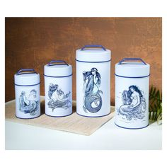 Set of 4 cylindrical tin canisters, lined for food safety and tight-fitting lids. Screenprinted, durable labels mermaid labels in beautiful ocean blue; 4 different mermaid designs. Sold only as a set