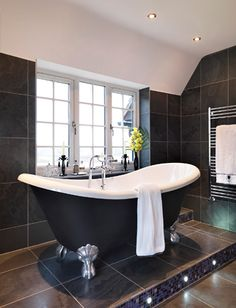 raised double-ended tub ... Don't really care for a black tub but I love bathtubs with feet