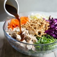 The Best Asian Salad Dressing - A photo of a brown dressing pouring over a bowl of various ingredients on a light background - click photo for full written recipe