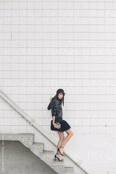 A woman walking down a flight of stairs dressed in all black by Stalman & Boniecka #stocksy #realstock
