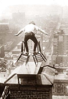 Balancing act on chimney of 22 story building in NY 1920s