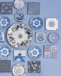 A mixture of plates and tiles, all in blue and white.