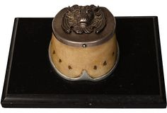 Unique hoof inkwell with decorative bull lid on a black marble base, circa 1800.
