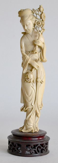 SUJET en ivoire sculpté, élégante au rameau fleuri. Socle en bois ajouré. Chine vers 1930. H. 25 cm