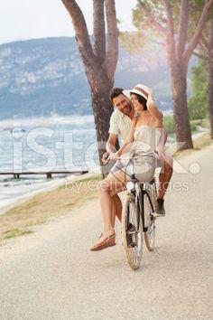 man carrying his woman on a bike in Garda lake royalty-free stock photo