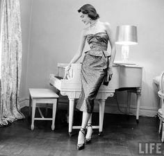Model with her piano in her new dress. Fashion Pattern, LIFE, July 7, 1949. Photographer: Nina Leen. The dress is the finished product. Leen photographed the original bolt of cloth, dress-making tools, patterns, and a mannequin to demonstrate the entire process of making a dress from a pattern. The model in the dress was present in many of the shots.
