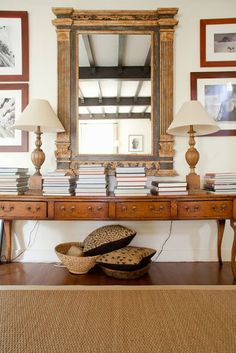 Don't have room for a full library? Take a page out of this design's book. A gorgeous statement mirror takes center stage, while books are stacked on a long wooden side table.