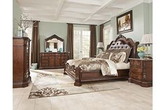 "The Ledelle Sleigh Bedroom Set from Ashley Furniture HomeStore (AFHS.com). With the traditional dark cherry stain finish flowing beautifully over the elaborately ornate details, the ""Ledelle"" bedroom collection features rich Ash swirl and Birch veneers along with Asian hardwoods and natural marble parquetry tops on the case pieces to create a sophisticated Old World style."