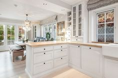 All white kitchen with long floor to ceiling windows