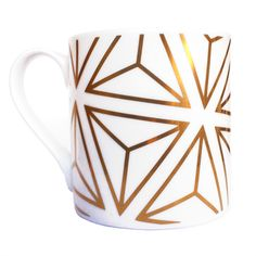 Alfred & Wilde Gold Tetrahedron Mug: This fantastic white fine bone china mug has been hand-decorated in Stoke-on-Trent with 9 carat gold.  The gold geometric tetrahedron pattern is based on the Platonic Solids, a series of five solid shapes named after the Ancient Greek thinker Plato. The solid shapes are symmetrical, and each is made up of faces that are the same shape.  Their mathematical beauty has led them to be repeatedly linked to the construction of the universe. They also symbolised…