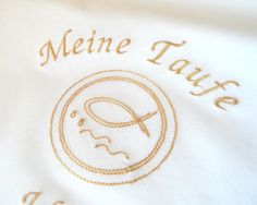 Wunderschönes weißes Tauf- oder Kerzentuch mit persönlicher Bestickung in Gold.  Das christliche Motiv zeigt als Symbol den Fisch (Ichthys), eines der ältesten Zeichen für Christen. Der Fisch, der im Wasser lebt, gilt als Symbol des Lebens und der Fruchtbarkeit und ist daher zur Taufe ein oft gewähltes Motiv.  Mit dem Namen des Kindes und dem Taufdatum bestickt, wird dieses Tuch ein Erinnerungsgeschenk an einen ganz besonderen Tag.