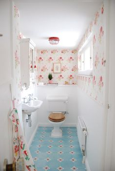 Gorgeous powder room. Pretty floral wall paper & blue tile.