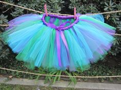 Little Mermaid Tutu! This tutu is made with lots of soft and fluffy Turquoise, Purple and Emerald Green tulle with a purple satin ribbon