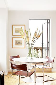 Dining space with wooden floors, brown leather chairs, white marble table, white walls, large glass door, colorful artwork, and large plants in a glass vase