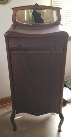 "eBay $50 theunusualsusspicks ANTIQUE Mahogany SHEET MUSIC CABINET.  late 1800's to  early 1900's.  We don't know what type of wood it is made from but it is a rich dark wood may be mahogany.  a partial paper sticker that reads Gately Furniture Co. on the back.  As the photos show, there is some ornate workmanship in places, and the drawer has a curved front/top and has a mirror on top. Pretty tassel drawer pulls. 19 wide x 14"" deep x 46"" high."