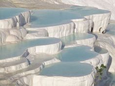 """Pamukkale is an amazing display of natural hot water pools  in Denizli Province, south-western Turkey. What you see in the photos below are known as travertines or the terraces that form due to the carbonate minerals that gather up as the flowing water circles. Pamukkale is actually Turkish for """"cotton castle"""", a name that we think manages to characterize the true inner """"fluffiness"""" of this place."""