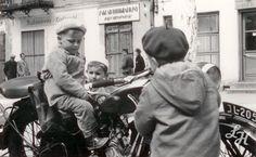 Dzieci na motocyklu. W tle widoczny szyld Zakładu Fotograficznego Jerzego Hryniewieckiego, który znajdował się przy głównej ulicy. Lata 60-te.