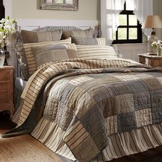 The Sawyer Mill bedding collection by VHC Brands. The simple block pattern in various plaids and stripes sets the perfect Farmhouse feel for the bedroom. The ensemble features shades of ash grey, creme, and black.