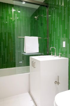 This glass enclosed shower features a bold accent with vertical emerald green rectangular tiles. A single white vanity boasts brushed nickel fixtures.