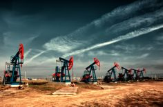 Oil and gas industry. Work of oil pump jack on a oil field. White clouds and…