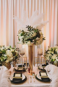 Tall, glass vases were spray-painted gold to match our Art-deco inspired reception. The metallic centerpiece was framed with glass candle holders which cased gold berries to keep with the color scheme.   See the rest of our Gatsby themed wedding, here! http://issuu.com/inbliss/docs/in_bliss-_pre-fall_2013?e=8049904%2F4363659