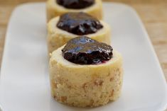 Vanilla Bean Mini Cheesecakes feature a toasted coconut crust, sweet, vanilla cheesecake, and a fresh blueberry sauce.(From Scratch<3)