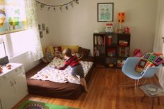 Check out George's super hip preschooler's bedroom — think floor bed, world map curtains, and lots of color! | Offbeat Families