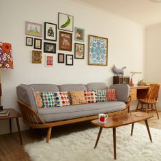 neutral furniture & furnishings paired with small throw pillows and collaged art in similarly small frames in similar colors (warm colors to match warm wood furniture). The subtle variety in colors and frame sizes makes it work.