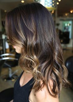 Medium-length dark brown hair with warm caramel highlights.
