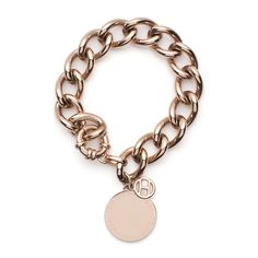 Fashionable statement - a rose gold chain bracelet with large, branded medallion and Tommy Hilfiger flag charm next to the spring ring clasp.
