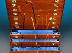 The function of this outstanding, custom-crafted mahogany cane cabinet is clear thanks to its beautifully inlaid decoration. Exotic woods were used to create lifelike, trompe l'oeil images of important walking sticks. Each of the 11 graduated drawers houses adjustable compartments for properly storing a wonderful collection of canes.  20th Century
