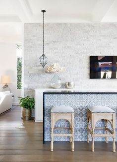 Modern Moroccan inspired kitchen with beautiful patterned tiles and moroccan styled high chairs