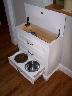 Made from small dresser. Pet food is kept in top with a scoop. Drawers hold all pet supplies with bowls integrated in the bottom drawer.