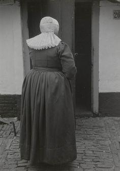 Antje Dorresteijn-Kuijer Soest 1952 in zondagse kerkdracht. Ze draagt over de zwarte ondermuts een cornetmuts, met daarover een lichtblauw 'lintentuigje'. In de ondermuts zijn trensjes gemaakt, waarin een paar mutsenbellen zijn gehaakt. Verder draagt ze een blauwe japon van 'Tibet' (wol), afgewerkt met zwart galon. Om haar hals een bloedkoralen snoer met gouden sluiting middenvoor, een jasseronketting met kruis, een dito met schuifje en medaillon en een broche. #Soest #Eemland #Utrecht…