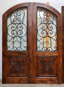 The Puerta Chapital double entry doors are made from alder wood and feature hand forged wrought iron and hand carved panels.