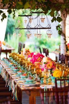 Coronas de hierro para colgar sobre la mesa y decoracion con cintas de colores bajo los platos