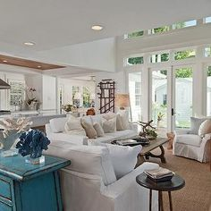mhkap - living rooms - beach living room, white slipcovered sofa, white slipcovered armchair, slipcovered sofa, beach pillows, beachy pillows, wooden trestle coffee table, trestle coffee table, bound sisal rug, hardwood floors, dark hardwood floors, mid-century modern console, two story living room, two story living room windows, patio doors, turquoise chest, distressed turquoise chest, coral, coral on acrylic stand, silver mirror, ornate silver mirror, deer mount, antler mounts, round end…