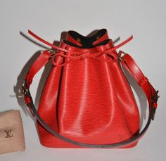 Authentic Louis Vuitton Epi leather Petit Noe in red with the original dust bag.   Epi leather is with small amount of very light scratches, otherwise, it is clean without marks. Epi leather on the bottom corners is with small amount of light abrasion. Epi leather on the top is without marks or wear. Leather leash is firm without marks or wear. Strap is firm without marks or wear. Lining is without marks or wear.   Date code:  AR0914   10.5 (height) x 10.25 (width) x 7.75 (depth)…