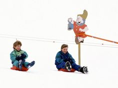 To the Slopes! The Best Royal Ski Trip Moments from Over the Years | BOMBS AWAY | Prince Harry (left) and Prince William went sledging down a mountain during a ski trip in Lech, Austria, in 1992.