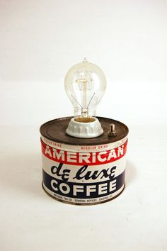 A coffee tin is more than simply a container. Each one represents a series of moments, an after dinner conversation, a holiday with family & friends, a meeting, or a summer camping trip all spent with a cup of coffee in hand. Show some respect to your coffee drinkin' ancestors with our American De Luxe Coffee Tin Lamp Our 'upcycled' lamp features a porcelain lamp holder, vintage reproduction 40W 'Edison style' filament bulb, push-button ON/OFF switch and a 6ft cord for those hard to rea...