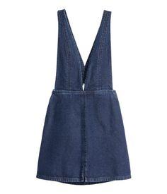 Kurzes Kleid mit tiefem V-Ausschnitt aus gewaschenem Denim. Rückenfreies Modell mit verstellbaren, hinten gekreuzten Trägern. Seitentaschen. Verdeckter Seitenreißverschluss und kurzer Schlitz vorn.