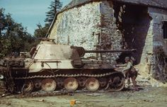 US soldier inspecting a destroyed Panther tank during the invasion of Normandy