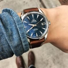 Omega Seamaster with blue dial on a brown leather strap.