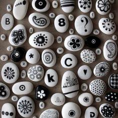 bemalte Steine mit schwarzen Motiven, Blumen und Buchstaben