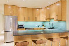 Elegant light wood modern kitchen with blue back splash and stainless steel appliances