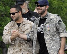 A couple of war veterans greet before throwing their medals towards McCormick Place, site of this weekend's NATO summit, during a rally in Chicago Sunday, May 20, 2012 in Chicago. (AP Photo/Charles Rex Arbogast)